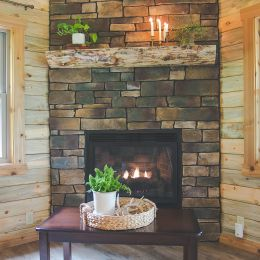 Floor to Ceiling Fire Place Covered in Stone Veneer with Log Mantle