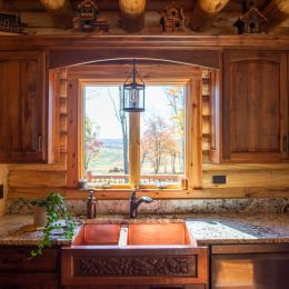 Log Home Kitchen with Stained Cabinets and Copper Farmhouse Sink