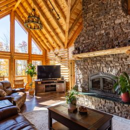 Great Room with Large Stone Covered Fireplace with a Log Mantle