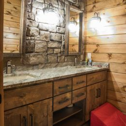 Upstairs full bathroom with stone veneer covered wall with custom vanity