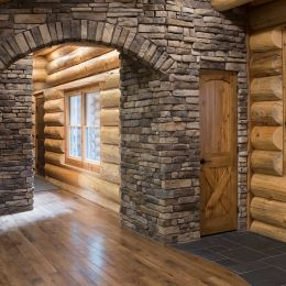 Stone veneer archway accenting against the swedish cope exterior logs