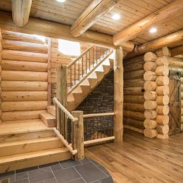 Quarter log stairway with log railings and black aluminum spindles