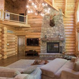 Log home great room with floor to ceiling fireplace and large antler chandelier