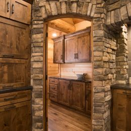 Stone Accents Encasing the Doorway to the Butler Pantry in this Custom Ktichen
