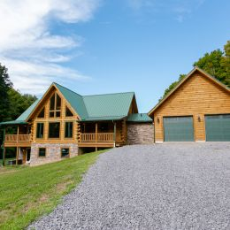 Log Home with Stone on Foundation and Breezeway with Green Roof