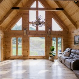 Log Home Great Room with Floor to Ceiling Windows