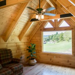 Open Loft Area with Large Window and Exposed Trusses