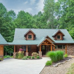 Log Home with Green Shingle Roof and Stone Exterior Accents