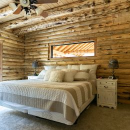Master Bedroom with Rusitc Log Walls and Rafters