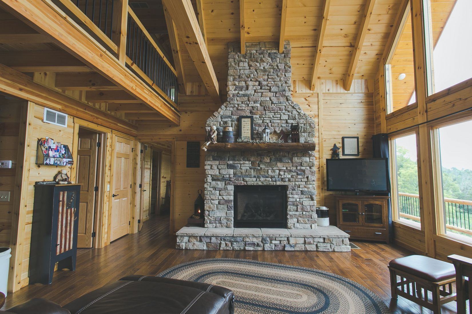 Stone Covered Fireplace with Log Mantle and Raised Hearth