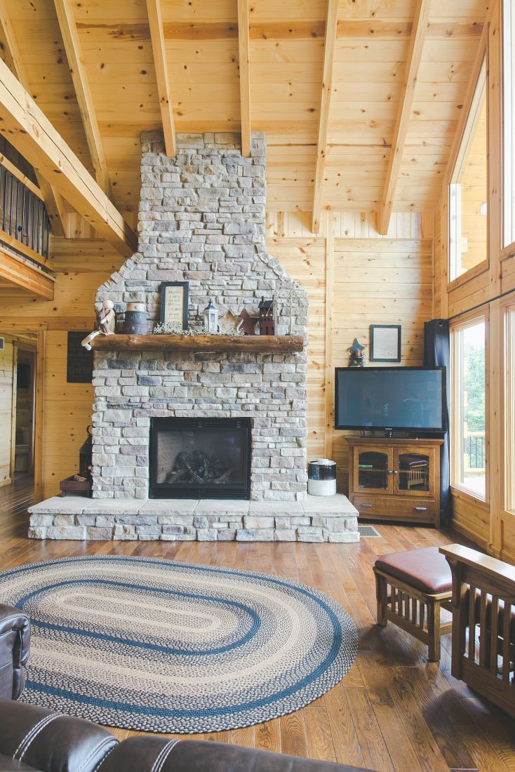 Gray Stone Covered Fireplace with Log Mantle and Raised Hearth