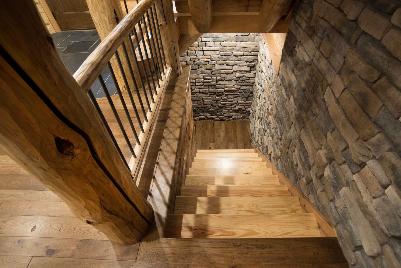 Stairs leading to the basement with stone covered accent wall