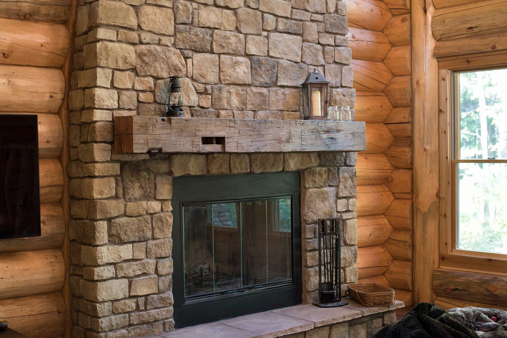 Stone covered fireplace with large wooden mantle and a raised hearth