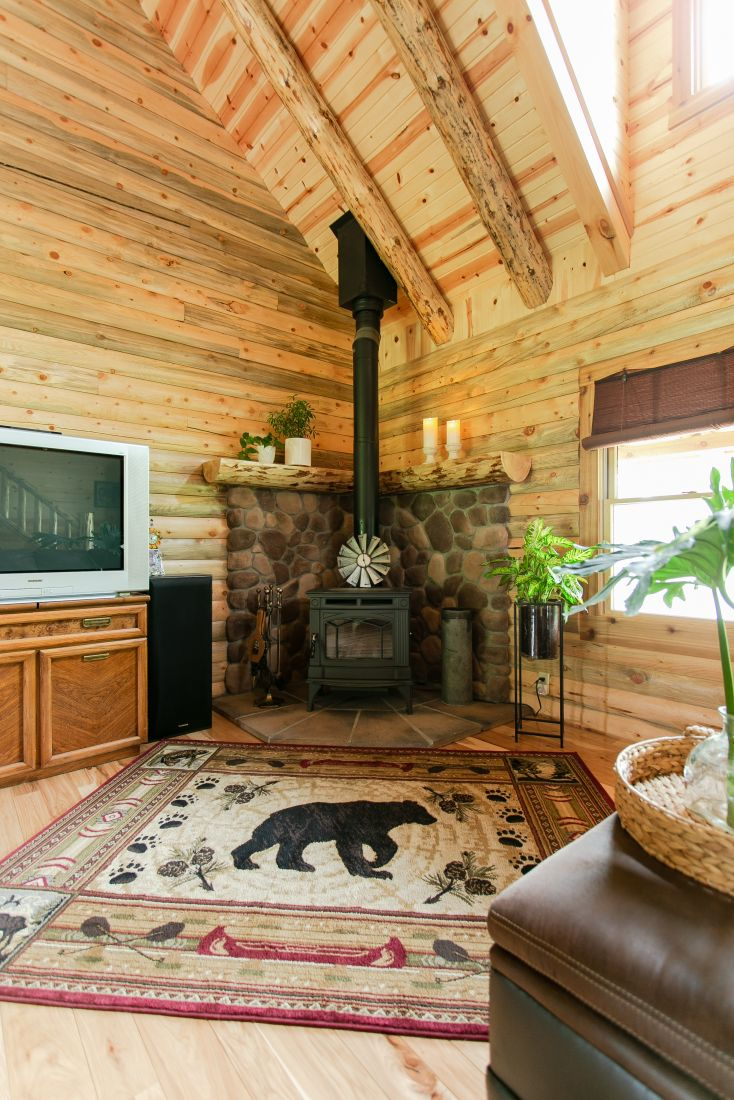 Wood burning stove with stone backdrop and log mantle
