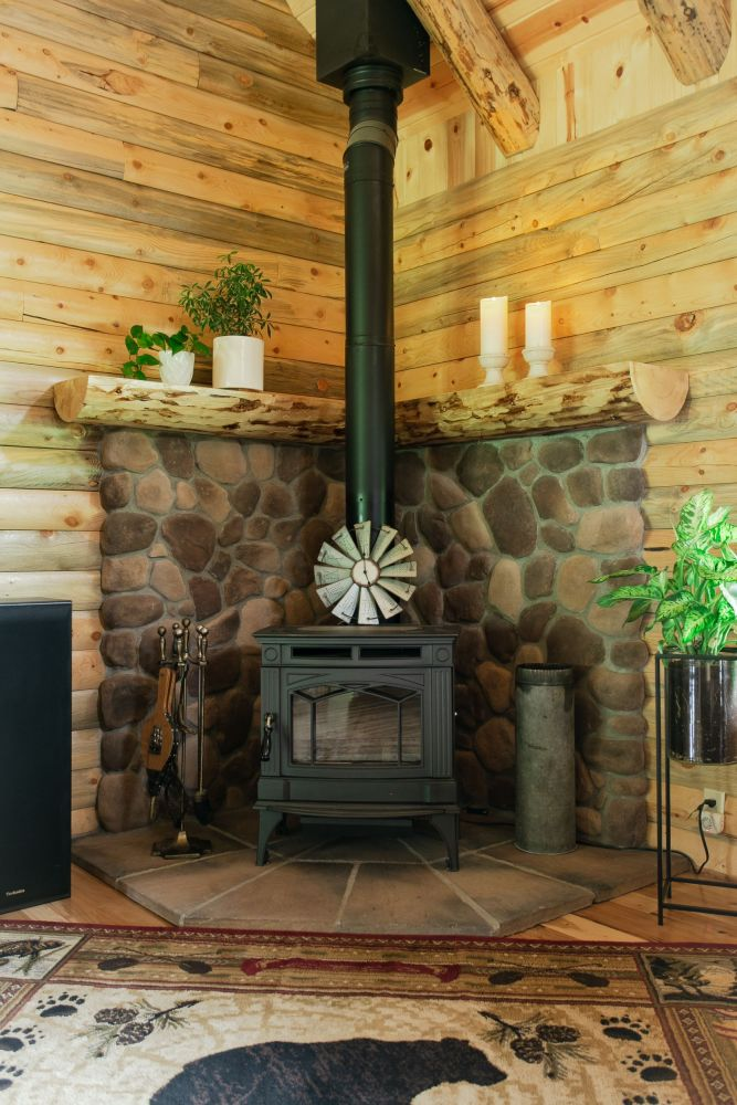 Wood Burning Stove with Stone Covered Raised Mantle Behind