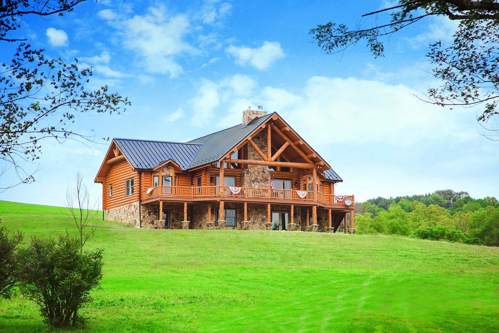 Swedish Cope Log Home with Black Metal Roof and Stone Covered Foundation
