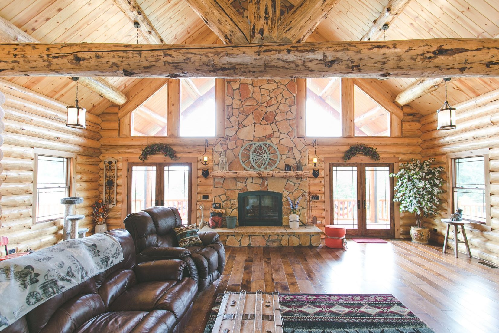 Log Home Living Room with Large Floor to Ceiling Fire Place