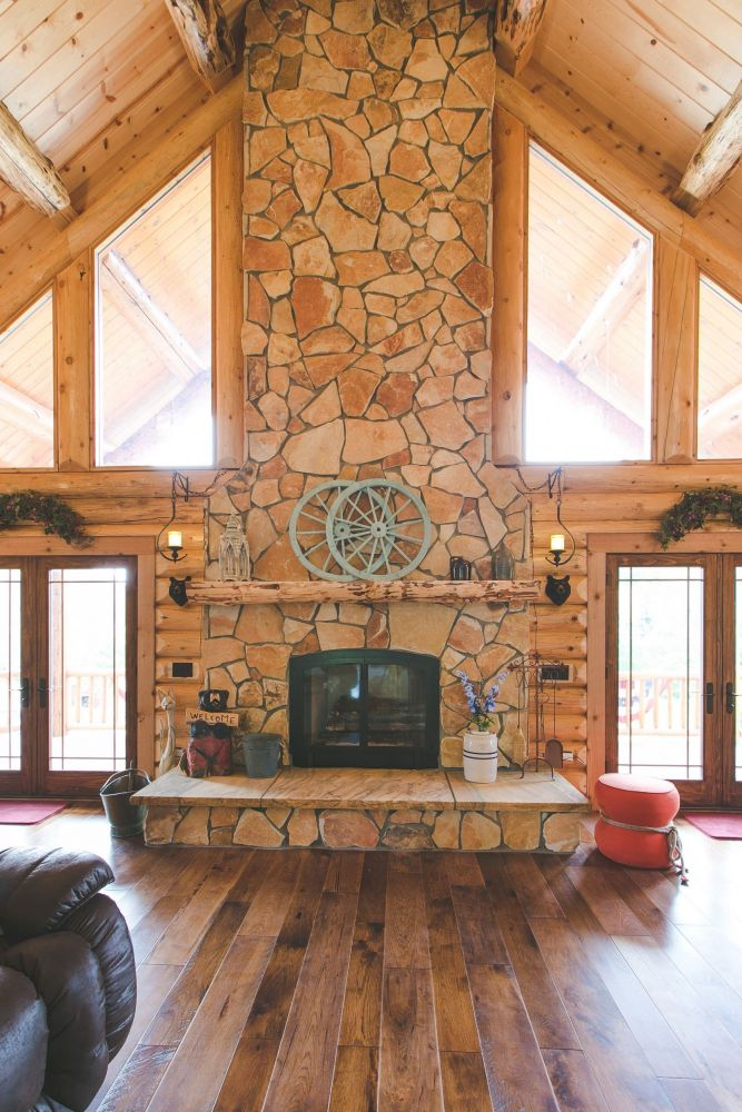 Stone Veneer covered fireplace with a log mantle and raised hearth