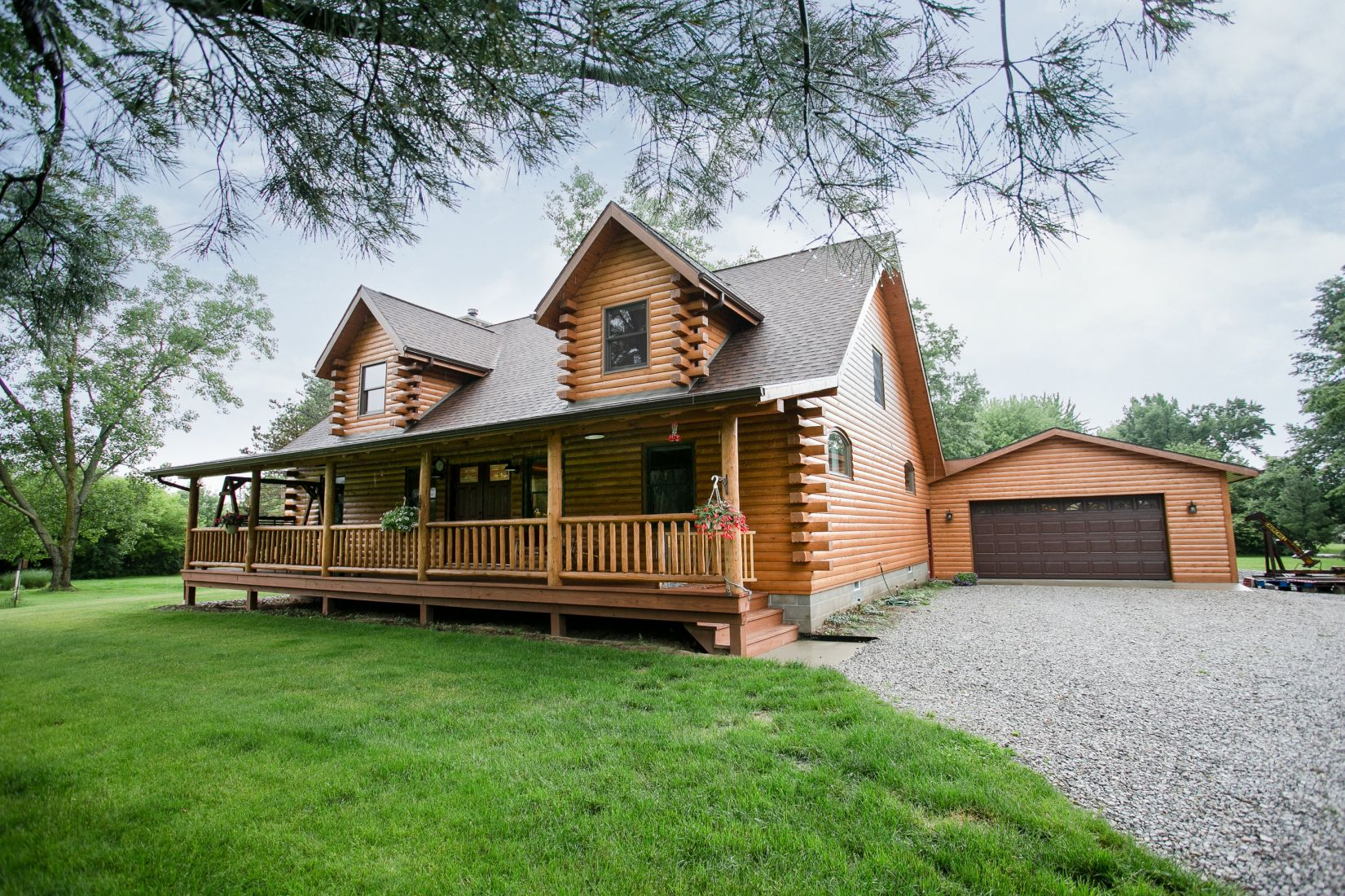 White Cedar Log Home with Brown Shingle Roof and Brown Entry Doors
